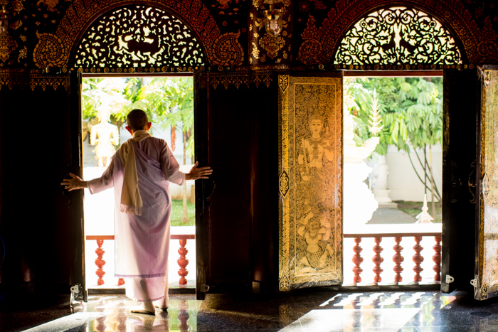 A porttrait of a Thai monk looking out a window - figure to ground photography