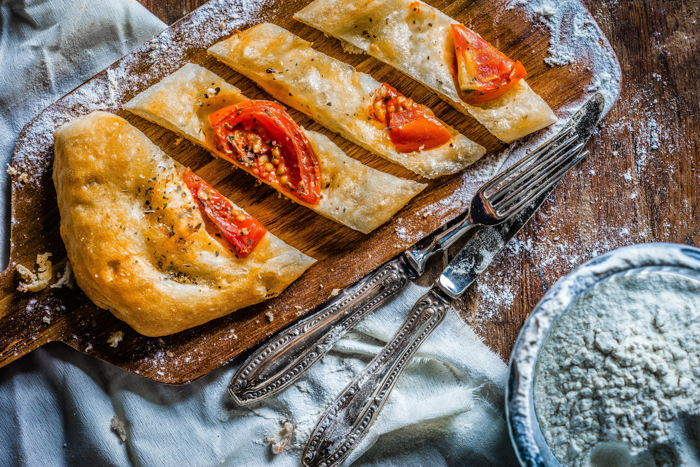 flatbread with tomatoes on a wood tray