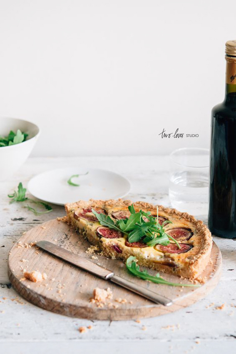 half pizza on a wooden tray on a white table with herbs on top beside a knife, a bottle of wine on the table
