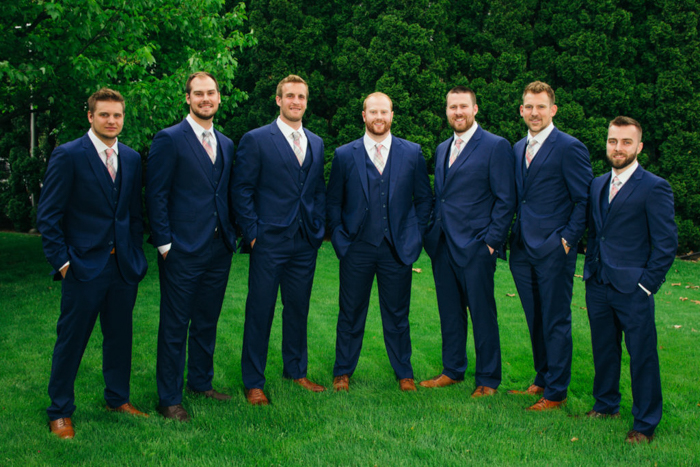 A group of groomsmen in blue black suits, in a curved line, posing in a grassy field, dark trees behind them