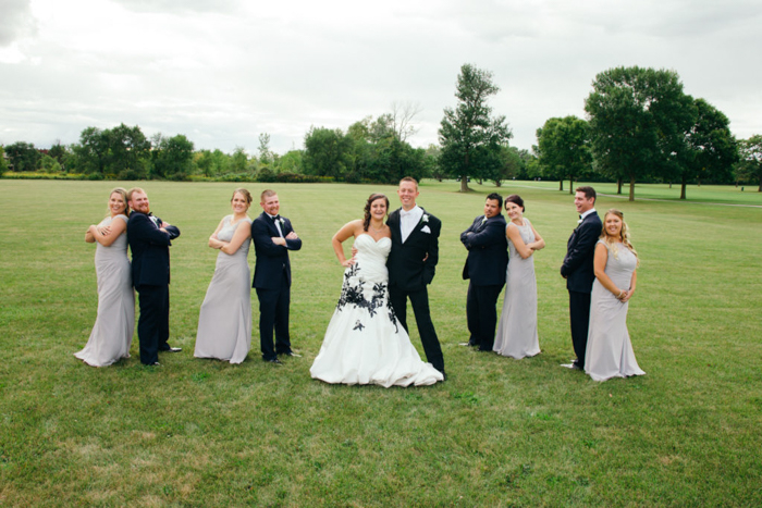 A wedding entourage in a wide grassy field, each couple standing back to back, the bride wearing a white wedding dress with intricate black embroidery