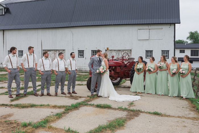 A large wedding party pose outdoors in a farmyard area- camera focus for sharp group photography