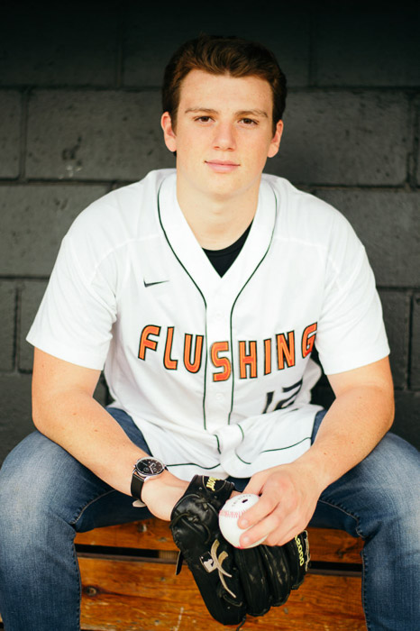 A male sports player posing for a portrait, hands relaxed between his legs holding sportsgear