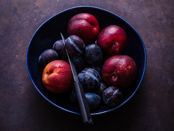 overhead food photo of a bowl of stone fruits