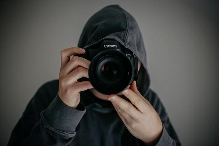 Photo of a guy in a hoodie with a camera
