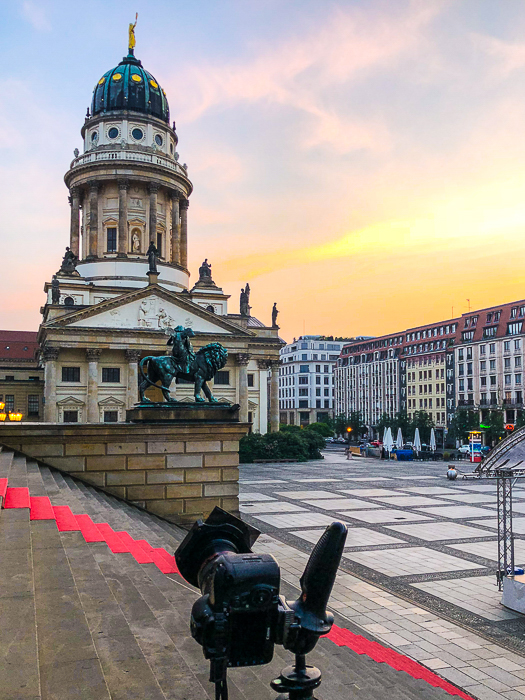 camera set up on a tripod at the steps at a square outside an old building with a blue dome, ready to take photos at sunset - stock photos that sell