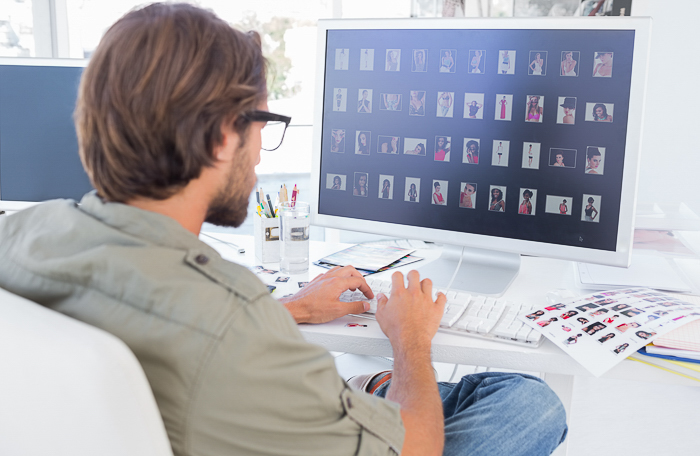 view from behind of a man sitting at his desk viewing several photos on a large computer screen