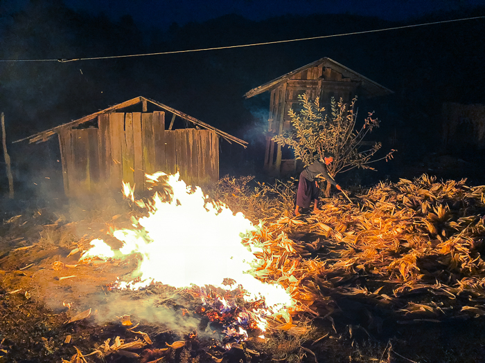 photo of a woman raking leaves into a bonfire near a wood cabin at night