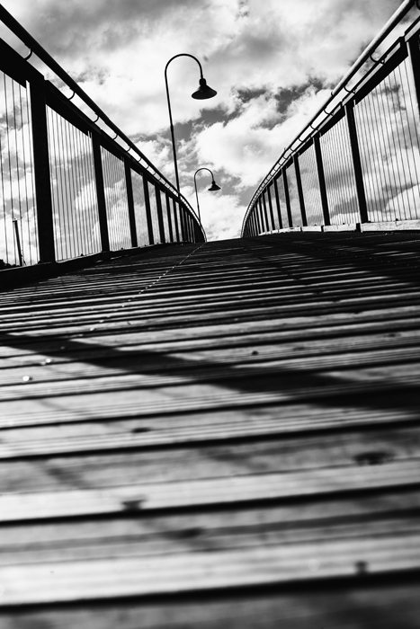 A black and white photo of a bridge with interesting composition