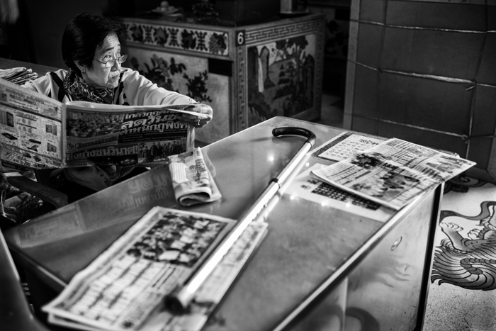black and white portrait of a woman reading a newspaper at a table
