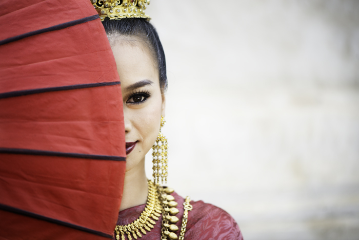 Interesting photography composition idea of a beautiful thai girl with half her face covered by an umbrella