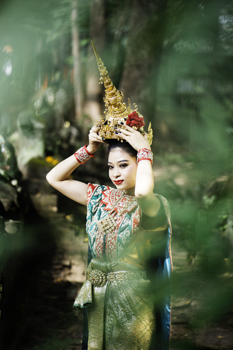 A photo of a Thai woman in traditional costume with a tree in the foreground.