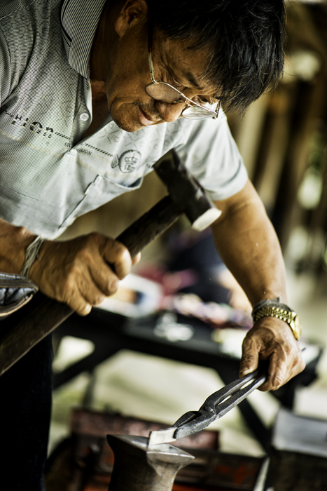A man hammering metal on an anvil - photography composition ideas