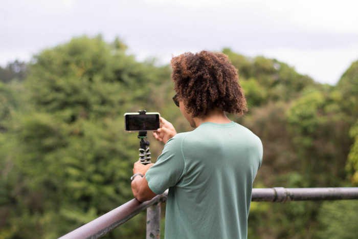 A person placing fixing their smartphone to a tripod to take a landscape shot