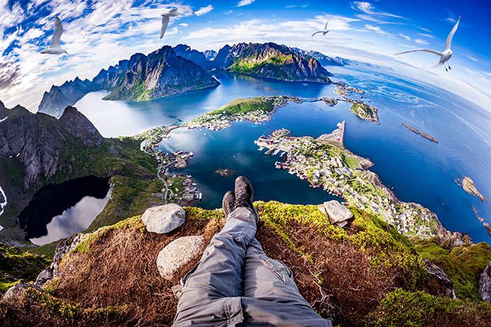 First person perspective shot from a hiker sitting at the edge of a cliff.