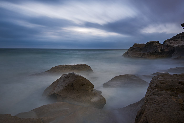 A long exposure ocean photography shot of rocks showing up through a foggy sea, a cloudy sky overhead