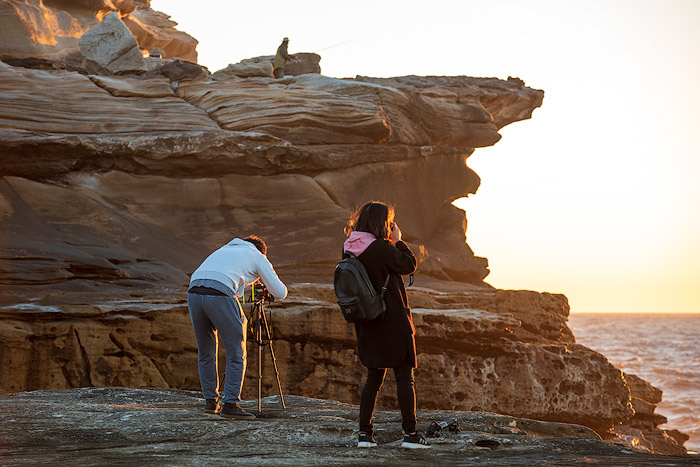 man and woman standing at a rocky cliff, setting up camera and tripod to photograph a seascape