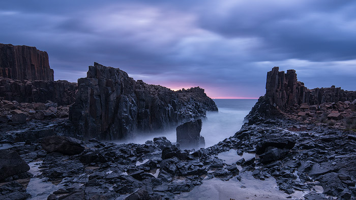 rocky sea shore, outcropping into foamy foggy sea, cloudy blue and pink sky during sunrise