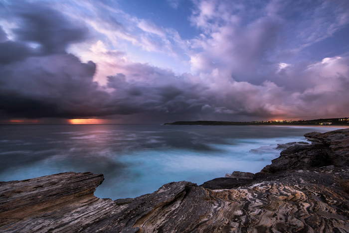 long exposure photo of a seascape at dusk. Blue seas with a rocky shore, reflecting the purple sky and clouds, the orange sunset on the horizon