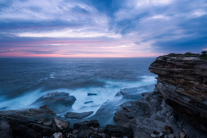 clifftop seascape. rocky cliff over looking a blue sea and foamy waves, a cloudy sky and purple pink sunrise on the horizon