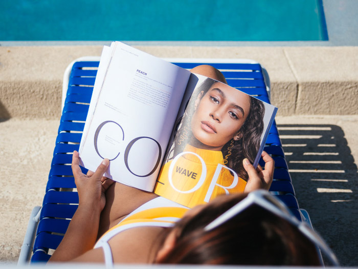 A girl reading a fashion magazine while sunbathing on a deck chair - magazine photographer tips