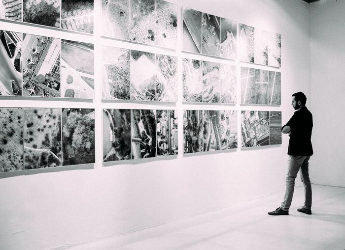 Photo of a guy looking at photos at a gallery