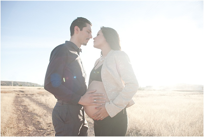 A romantic photo of pregnant couple outdoors, the bright sun behind them