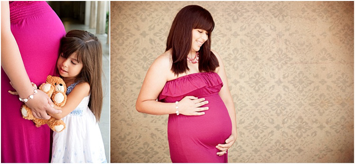 maternity photoshoot, pregnant woman in a pink dress, her daughter hugging her round her belly