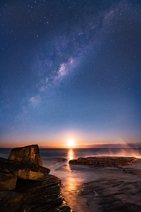 Stunny night photo of the moonrise and milky way by a coastal seascape