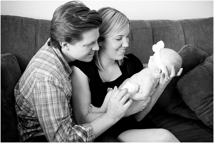 black and white photo of parent sitting on a sofa holding newborn
