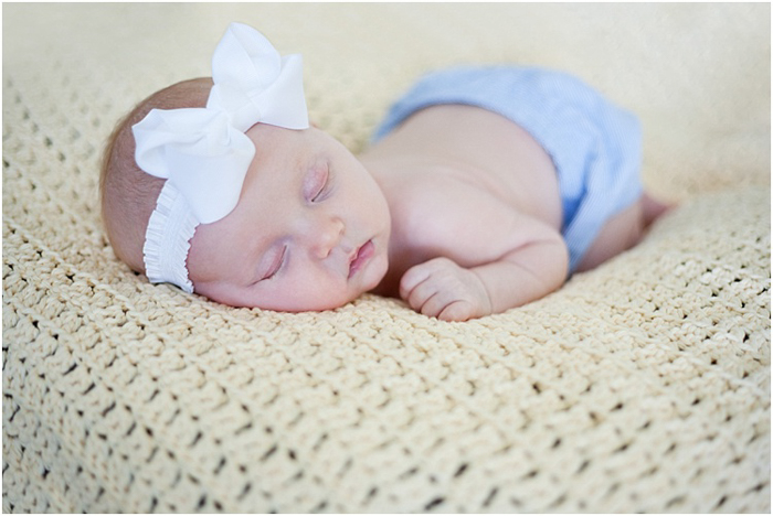 sleeping baby in a blue diaper and white headband