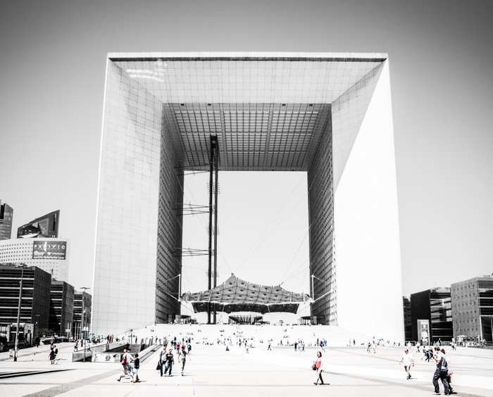 An overexposed photo of an architectural landmark and passers by