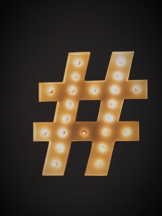 A golden instagram hashtag on black background