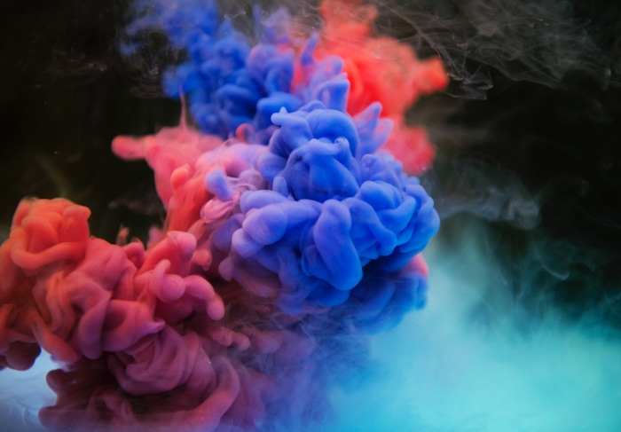 Colourful clouds of smoke against a dark background