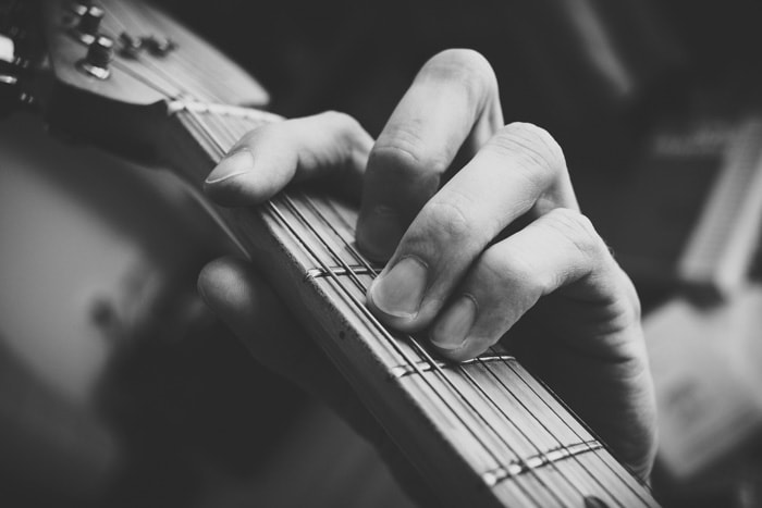 A close up black and white photo of a persons hand playing guitar