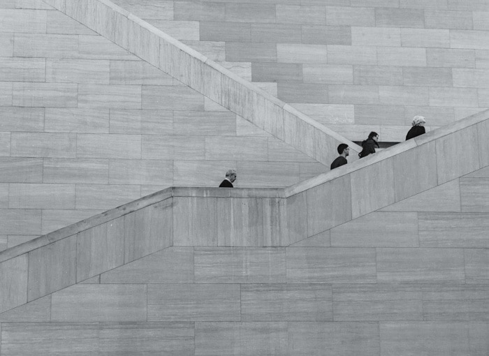 Black and white photo of four people climbing stone stairs