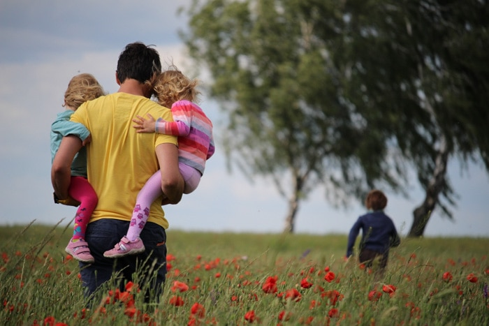 A family walking through a poppy field