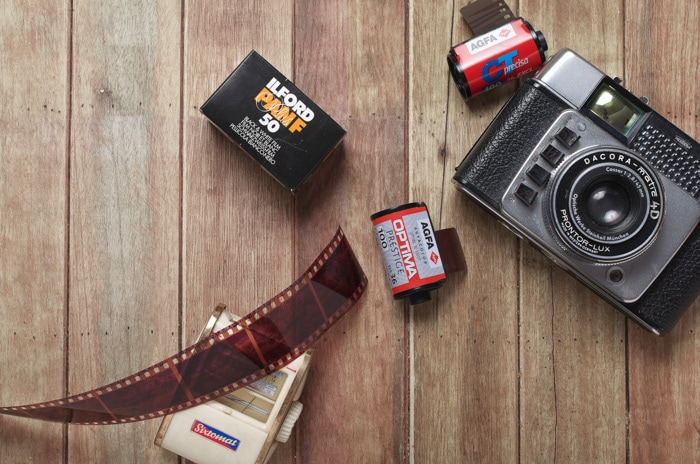 flat lay of a film camera and rolls of film on a wooden background