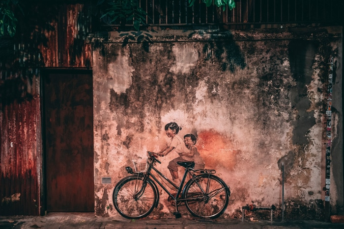 Atmospheric photo of a mural of two children on a bike on a stone wall in low light