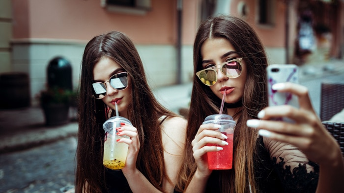 Two girls wearing sunglasses and drinking juice taking a selfie for Instagram
