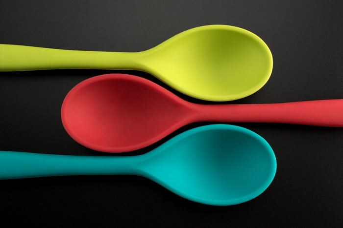 flat lay product photography shot of three colored spoons against a grey background
