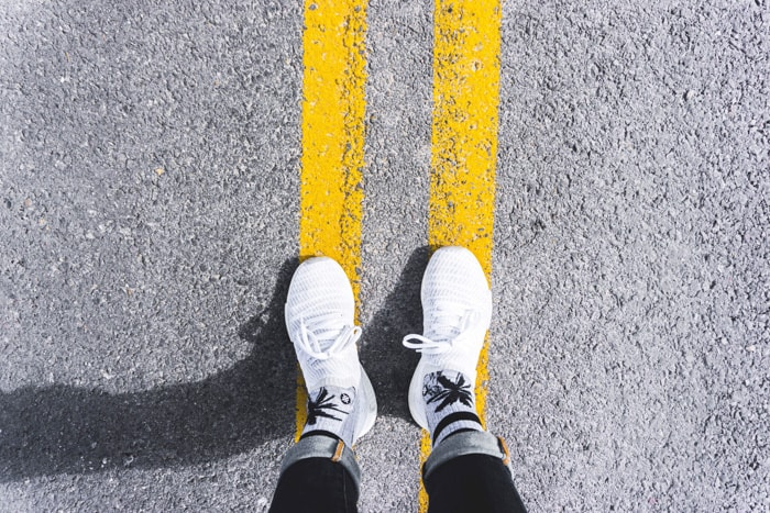 Overhead shot of a persons feet standing on yellow double lines on a roadway - best photography hashtags for Instagram success