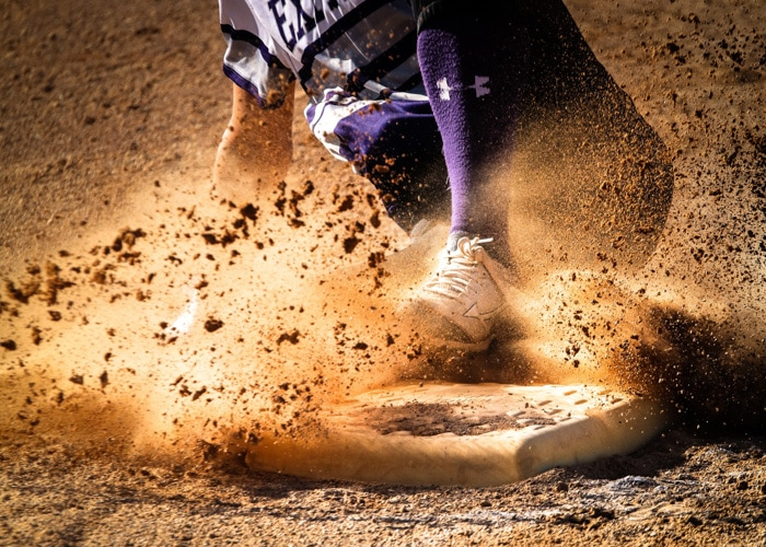 Action photo of a sports person sliding in the dirt