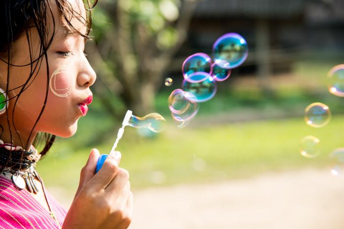 close up portrait of a little girl blowing bubbles - portrait photography props