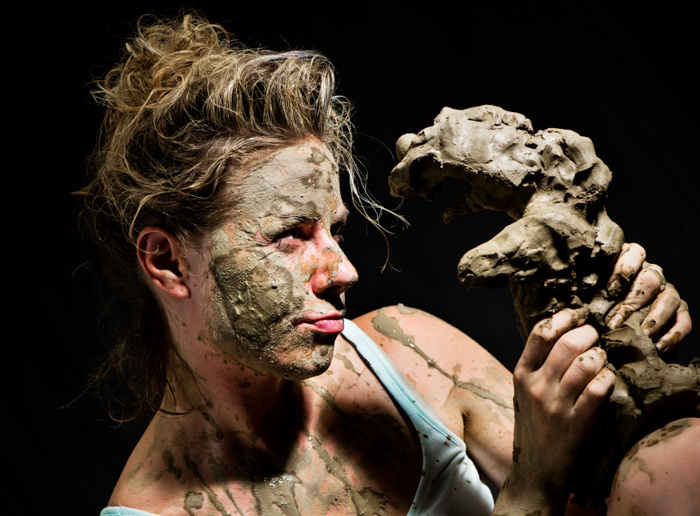 a portrait of a female ceramic artist working with clay as photography props