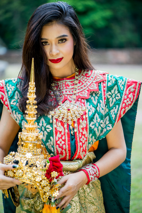 A beautiful female model in Classical Thai costume holding photography props for extra impact