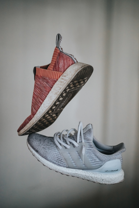 styled photo of red and grey running shoes against a white grey background