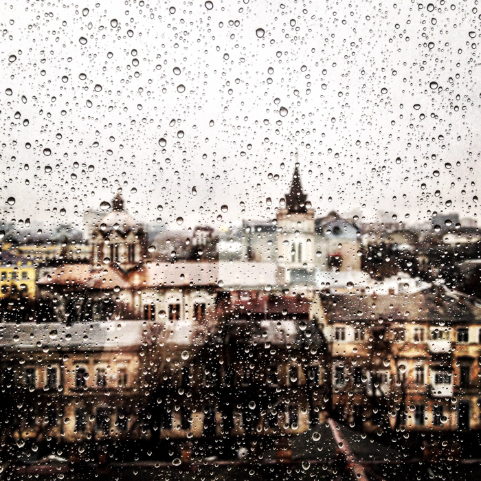 A cityscape seen through a rain splattered window