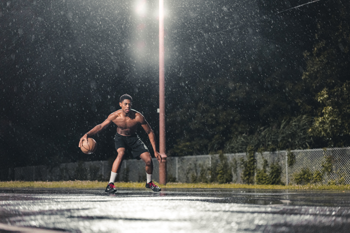 Atmospheric rain photography of a man playing basketball at night