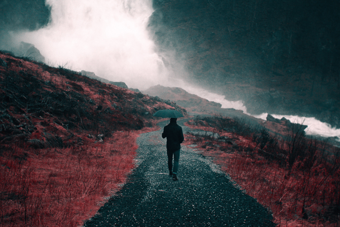 Dark and moody rain image of a person walking through a landscape with an umbrella